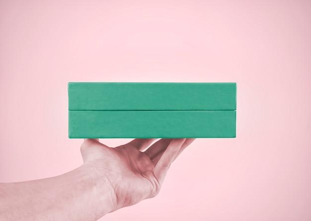 Caixa de presente na mão masculina. cores pastel.