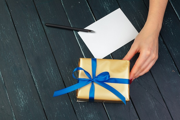 Caixa de presente na mão meninas na mesa de madeira