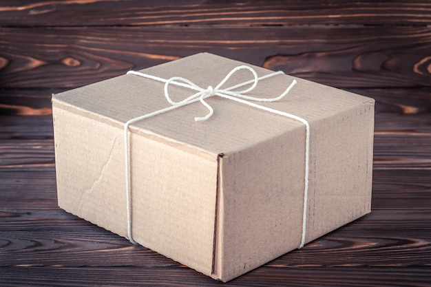 Caixa de presente na mesa de madeira marrom. conceito de serviço de entrega de encomendas. caixa de papelão com laço de corda.