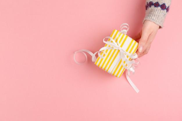 Caixa de presente nas mãos femininas na rosa