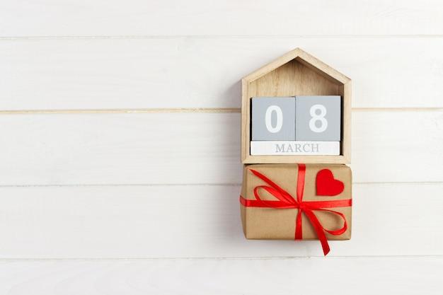 Caixa de presente no calendário de blocos de madeira com coração vermelho brilhante, 8 de março, comemorando o dia internacional da mulher