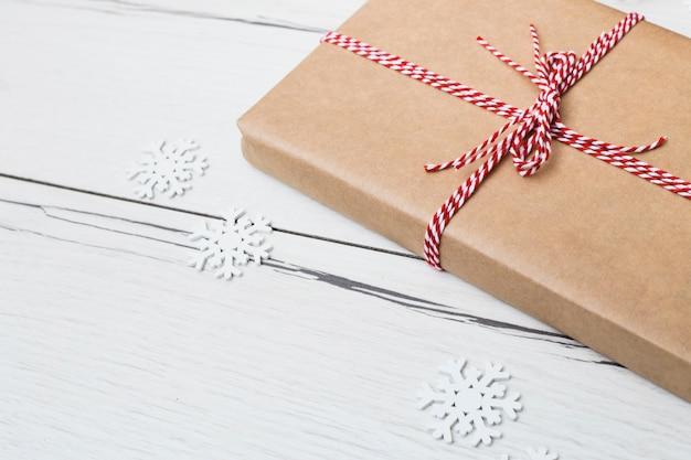 Caixa de presente no envoltório perto de flocos de neve de papel
