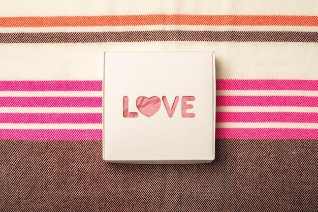 Caixa de presente no fundo de uma textura de tecido multicolorido. composição do dia dos namorados. bandeira. camada plana, vista superior.