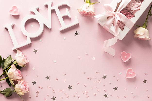 Caixa de presente ou caixa de presente e flores na vista de mesa rosa.