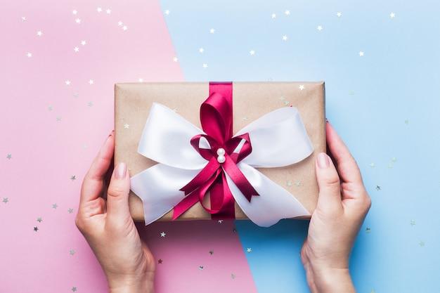Caixa de presente ou presente com um grande laço nas mãos de uma mulher em uma mesa azul e rosa. composição plana leiga para o natal, aniversário, dia das mães ou casamento.