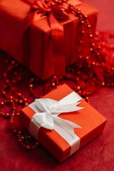 Caixa de presente para mulheres românticas com fita enrolada na mesa vermelha