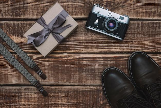 Caixa de presente para o dia dos pais com acessórios masculinos, câmera retro, suspensórios e sapatos de couro em uma mesa de madeira. postura plana.