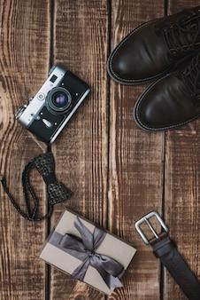 Caixa de presente para o dia dos pais com acessórios masculinos gravata borboleta, câmera retro, cinto e sapatos de couro em uma mesa de madeira. postura plana.