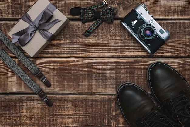 Caixa de presente para o dia dos pais com acessórios masculinos gravata borboleta, câmera retro, suspensórios e sapatos de couro em uma mesa de madeira. postura plana.