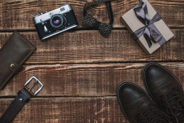 Caixa de presente para o dia dos pais com acessórios masculinos gravata borboleta, carteira, câmera retro, cinto e sapatos de couro em uma mesa de madeira. postura plana.