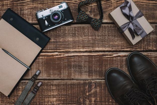 Caixa de presente para o dia dos pais com acessórios masculinos gravata borboleta, carteira, câmera retro, suspensórios e bloco de notas e sapatos de couro em uma mesa de madeira. postura plana.
