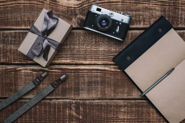 Caixa de presente para o dia dos pais com acessórios masculinos gravata borboleta, carteira, câmera retro, suspensórios e bloco de notas em uma mesa de madeira. postura plana.