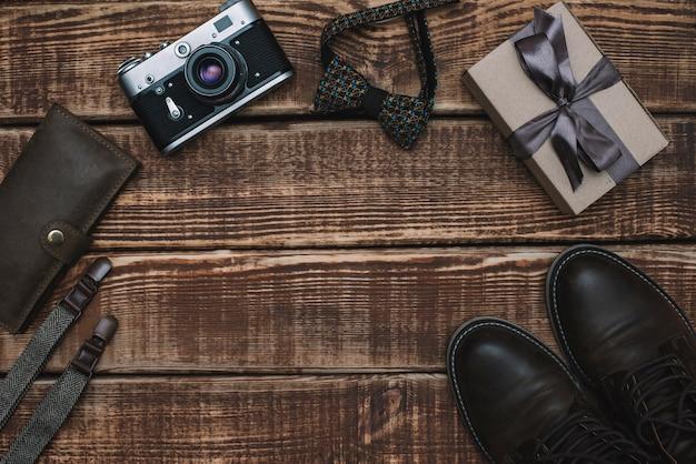 Caixa de presente para o dia dos pais com acessórios masculinos gravata borboleta, carteira, câmera retro, suspensórios e sapatos de couro em uma mesa de madeira. postura plana.