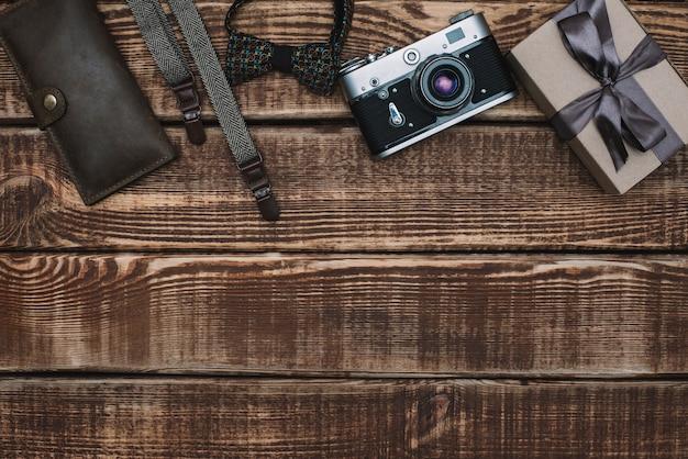 Caixa de presente para o dia dos pais com acessórios masculinos gravata borboleta, carteira, câmera retro, suspensórios em uma mesa de madeira. postura plana.
