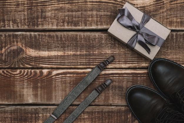 Caixa de presente para o dia dos pais com acessórios masculinos, suspensórios e sapatos de couro em uma mesa de madeira. postura plana.