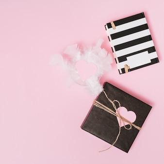 Caixa de presente, penas com coração de ornamento na placa e notebook