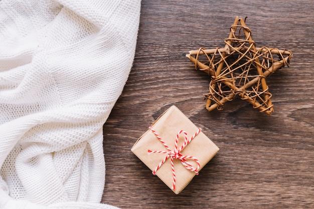 Caixa de presente pequena com estrela de madeira na mesa