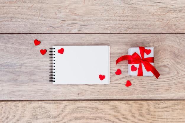 Caixa de presente pequena com o bloco de notas e corações na mesa