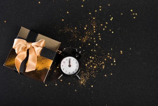 Caixa de presente pequena com relógio na mesa preta