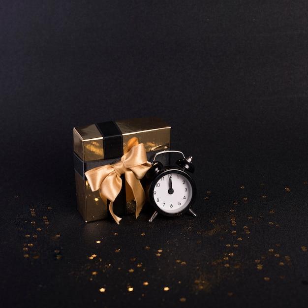 Caixa de presente pequena com relógio na mesa