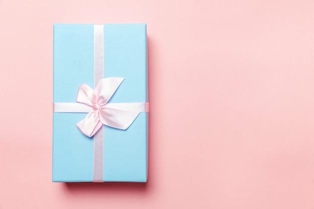 Caixa de presente pequena embrulhada em papel azul isolado em rosa pastel colorido moderno
