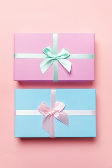 Caixa de presente pequena embrulhada em papel rosa e azul isolada em rosa pastel colorido moderno