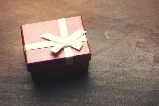 Caixa de presente pequena vermelha na mesa de madeira