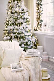Caixa de presente perto da árvore de natal decorada na sala de estar