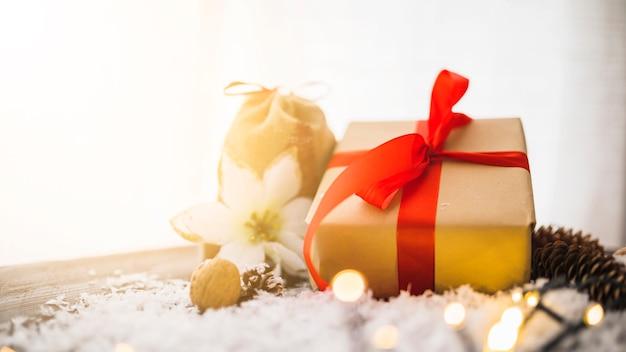 Caixa de presente perto de flores e senões entre neve decorativa