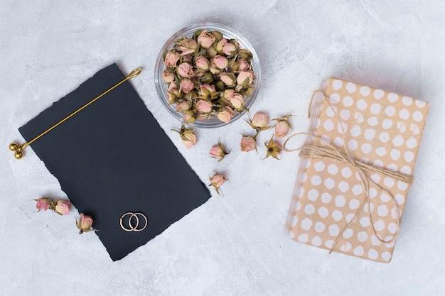 Caixa de presente perto de papel preto e conjunto de flores secas