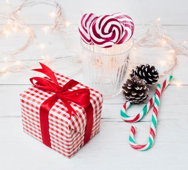 Caixa de presente perto de vidro com pirulitos, bastões de doces e luzes de fadas