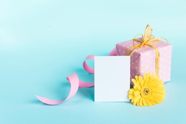 Caixa de presente pontilhada rosa, flor amarela do gerbera e cartão vazio sobre o azul.