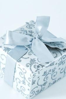 Caixa de presente prata com laço no fundo branco
