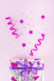Caixa de presente prata com serpentinas enroladas, forma de estrela e confetes contra fundo rosa