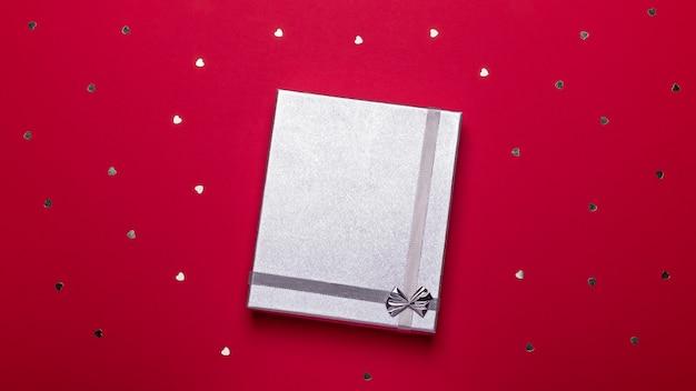 Caixa de presente prata sobre fundo vermelho escuro com confetes de corações, vista superior