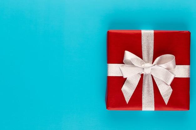Caixa de presente presente na vista superior do plano de fundo vermelho. composição plana leiga para aniversário, dia das mães ou casamento.