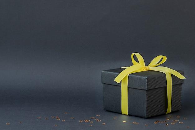 Caixa de presente preta com fita amarela em fundo preto