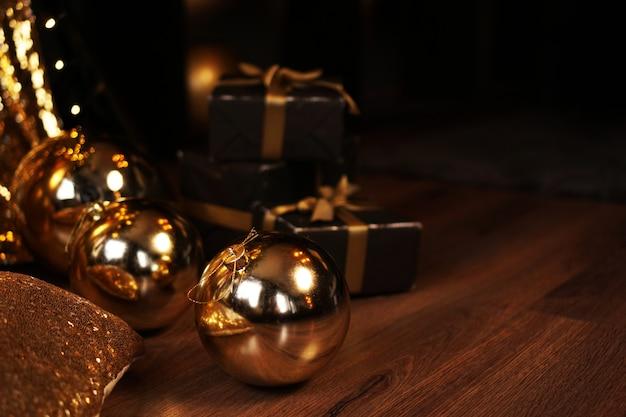 Caixa de presente preta com fita dourada e grandes bolas de ouro de ano novo em fundo preto para o cartão. composição festiva de inverno com espaço de cópia.