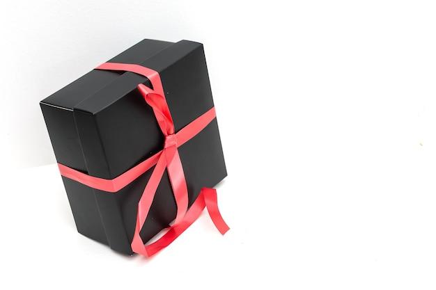 Caixa de presente preta com fita e laço de cetim vermelho sobre fundo branco.