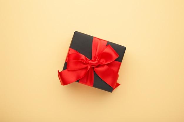 Caixa de presente preta com fita vermelha e laço bege.