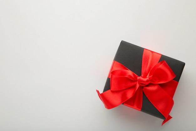Caixa de presente preta com fita vermelha e laço em cinza.