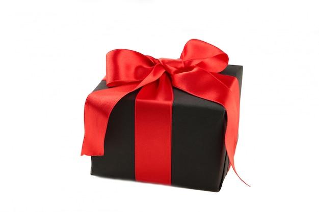 Caixa de presente preta com fita vermelha e laço isolado no branco.