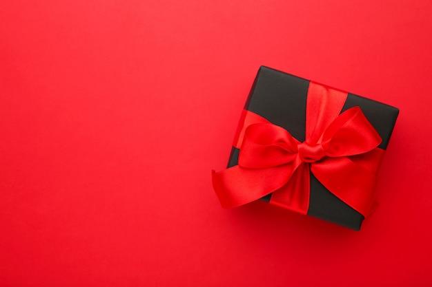 Caixa de presente preta com fita vermelha e laço vermelho.