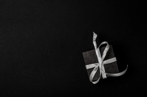 Caixa de presente preta com laço de fita de prata sobre fundo preto.