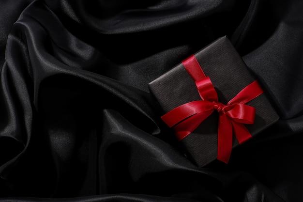 Caixa de presente preta com laço vermelho