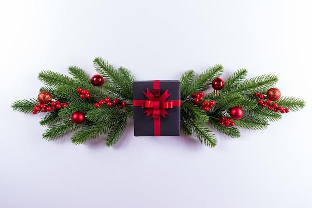 Caixa de presente preta com ramo de abeto em fundo branco. fundo de natal.