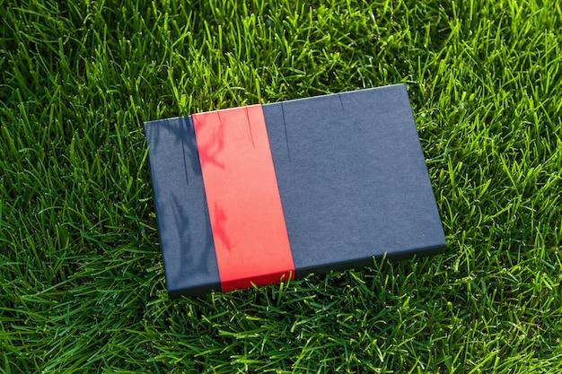 Caixa de presente preta com uma faixa vermelha deitada na grama. caixa de presente na grama.
