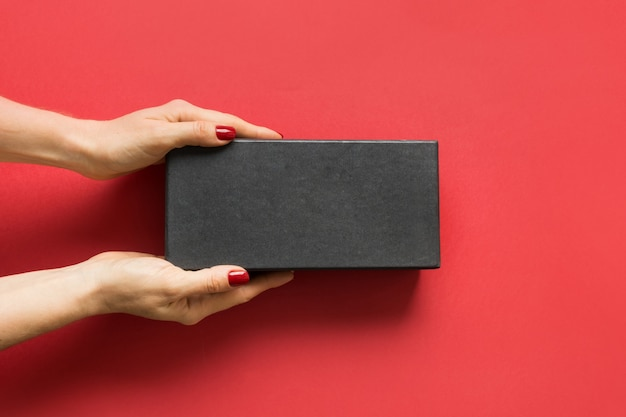 Caixa de presente preta nas mãos femininas no vermelho. dia dos pais. dia de boxe. sexta-feira preta.