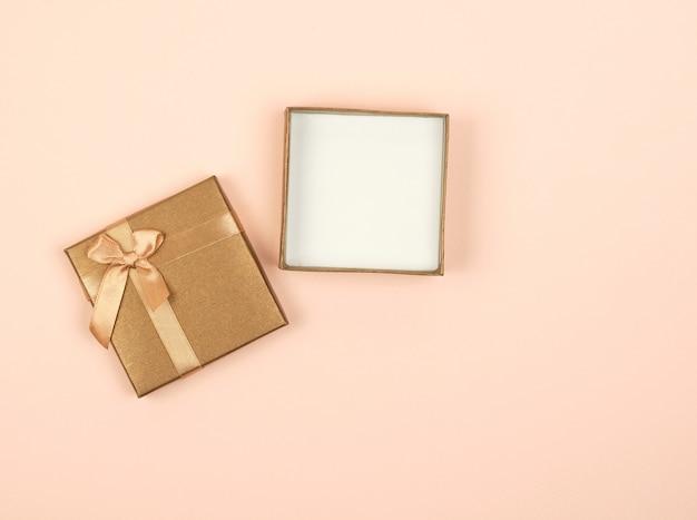 Caixa de presente quadrada dourada aberta com um arco