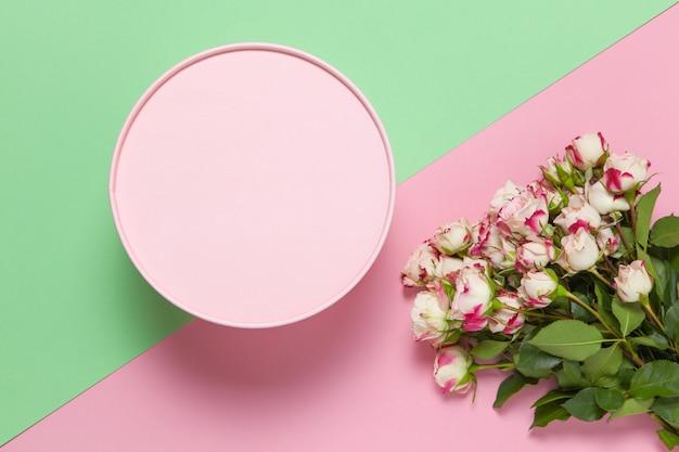 Caixa de presente redonda rosa, buquê de rosas pequenas em fundo pastel de duas cores rosa e verde, cópia espaço